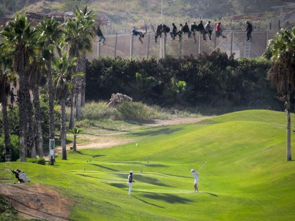 The stark contrast between white golfers and African immigrants scaling security fences.