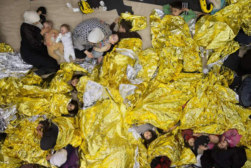 Syrian refugees sleeping on an Italian navy ship after being rescued from a fishing vessel carrying 443 Syrian asylum seekers.