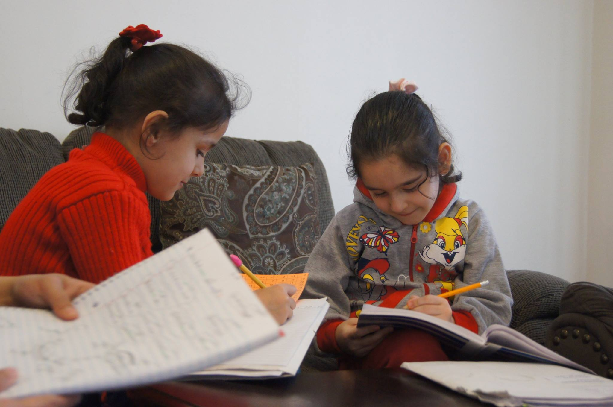 Shahd, 7, (in red) and Shaema, 4, completing their homework while volunteer from RefugeeOne teaches her mother and siblings English.
