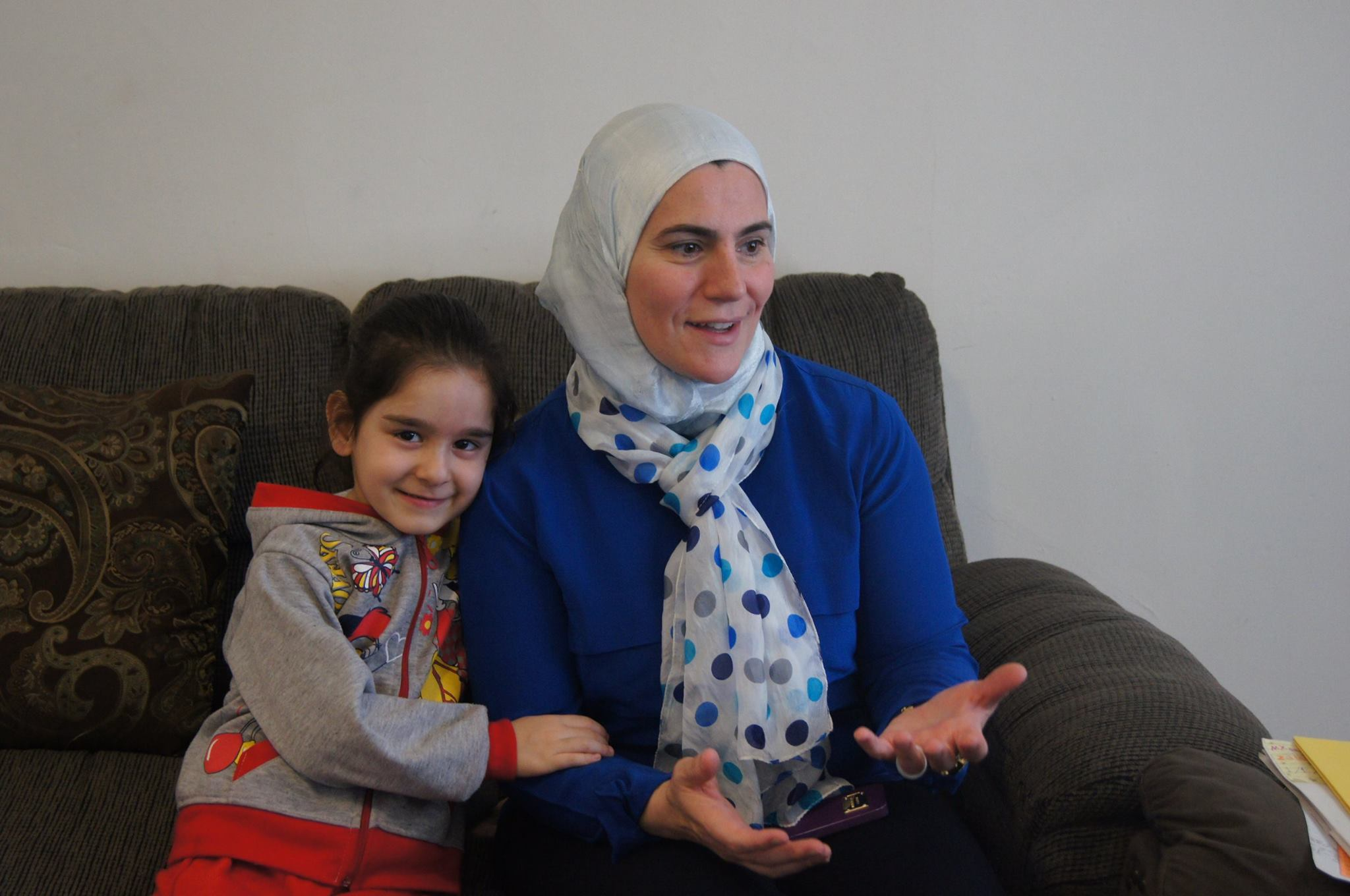Suzanne Akhras, founder of Syrian Community Network, meets with the family to help them adjust to living in the US.